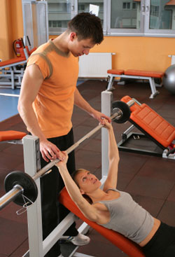 man spotting woman doing incline bench press