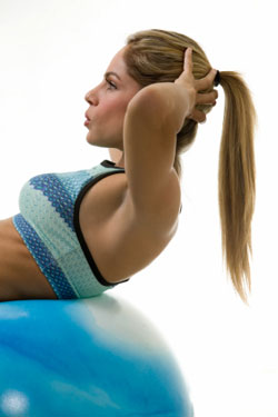blond woman doing abdominal exercise on exercise ball