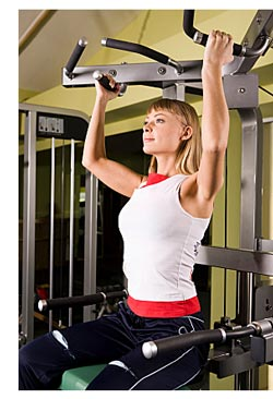 blond woman using exercise machine