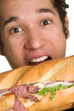 man eating a huge sandwich