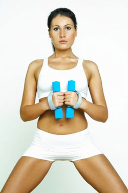 woman in white shorts holding dumbbells