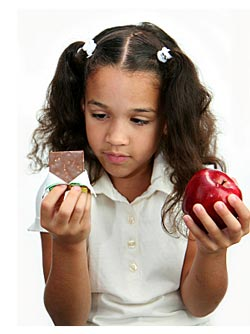 young girl choosing between candy bar and apple