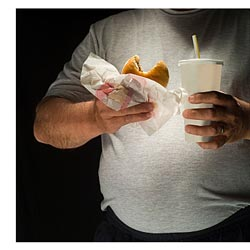 overweight man eating fast food