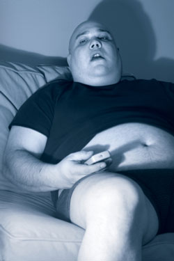 overweight man stuporous in front of television
