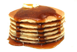 large stack of pancakes with syrup
