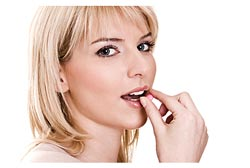 blond woman taking a pill