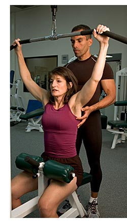 woman with a trainer doing pulldowns