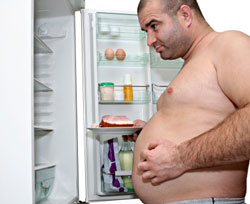 overweight man looking in refrigerator