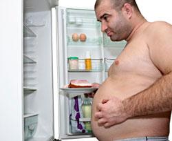 overweight man looking in refrigerator