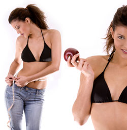 woman in bikini top measuring waist and eating an apple