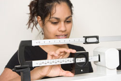 woman weighing self on doctor's scale