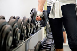 rack of dumbbells with person holding one dumbbell