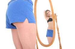 woman looking at her body in the mirror