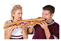 woman helping man who is eating an enormous sandwich