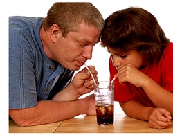 two people drinking from glass with separate straws