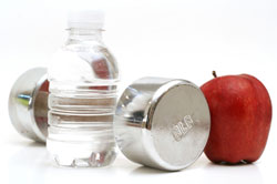 water bottle, dumbbell and and apple